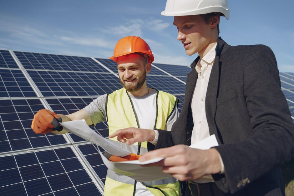 Two men looking at plans in front of some solar panels